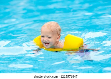 Baby with inflatable armbands in swimming pool. Little boy learning to swim in outdoor pool of tropical resort. Swimming with kids. Healthy sport activity for children. Summer vacation. Swim aids.