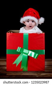 Baby inside a gift box, with a Santa Claus hat