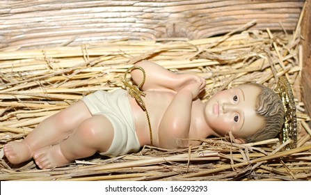 Baby Jesus is laid in the cradle in a manger with folded hands praying