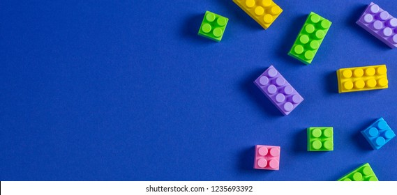 Baby kid toys background. Colorful plastic construction blocks on blue background