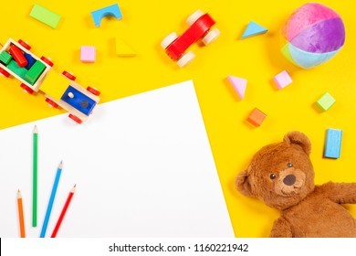 Baby kids toys background. Blank white card, colored pencils, wooden and soft toys on yellow background. Top view