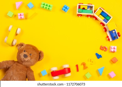 Baby kids toys background with teddy bear, wooden train, colorful blocks and bricks on yellow background. Top view