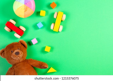 Baby kids toys background with teddy bear, wooden cars, colorful blocks and bricks on green background