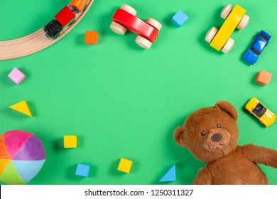 Baby kids toys background with teddy bear, wooden cars, train, colorful blocks and bricks on green background