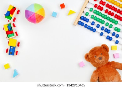Baby kids toys background with teddy bear, wooden train,toy abacus and colorful blocks. Top view, flat lay