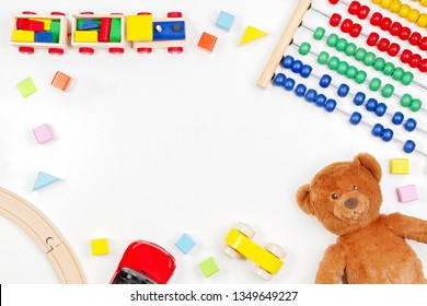 Baby kids toys background with teddy bear, toy tools, wooden train, cars and colorful blocks. Top view, flat lay.