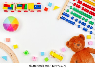 Baby kids toys background with teddy bear, toy tools, wooden train, cars and colorful blocks. Top view, flat lay