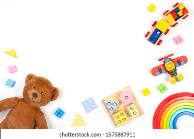 Baby kids toys background. Teddy bear, wooden educational stacking color recognition puzzle toy, wooden train, teddy bear and colorful blocks on white background. Top view, flat lay