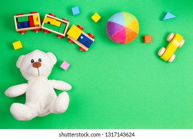 Baby kids toys background. White teddy bear, wooden toy train, car and colorful blocks on green background. Top view, flat lay