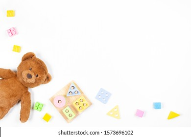 Baby kids toys background. Wooden educational geometric stacking blocks shape color recognition puzzle toy, teddy bear and colorful blocks on white background. Top view, flat lay