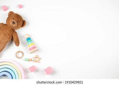 Baby kids toys frame on white background. Teddy bard and wooden educational toys on desk. Top view. Flat lay