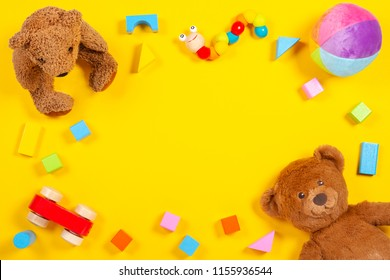 Baby kids toys frame with teddy bear, wooden toy car, colorful bricks on yellow background. Top view