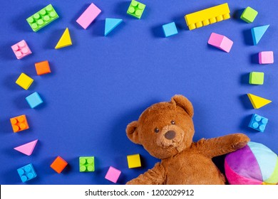 Baby kids toys frame with teddy bear, colorful ball, bricks and cubes on blue background. Top view