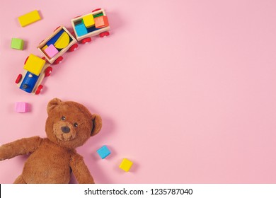 Baby kids toys frame with teddy bear, wooden train, colorful bricks on pink background