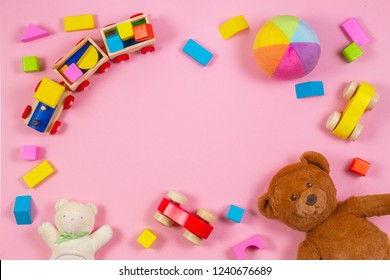 Baby kids toys frame with teddy bear, toy car, wooden train, colorful bricks on pink background. Top view
