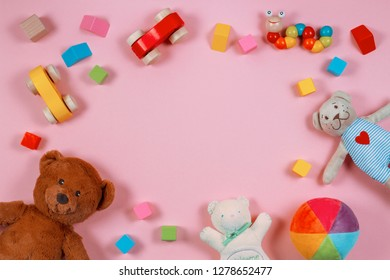 Baby kids toys frame with teddy bear, colorful wooden blocks on pink background. Top view