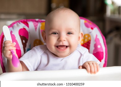 Baby in the kitchen in a baby chair holding a spoon and smiling.Sweet baby in high chair.Cheerful baby child eats food itself with spoon. Portrait of happy kid boy in high chair.first teeth