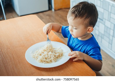 Baby in the kitchen eagerly eating pasta with a fork and hands, very neat