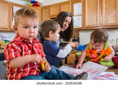 Baby in kitchen with guilty face looks at camera