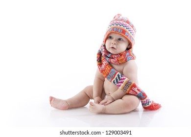 baby in knitted hat, scarf and diaper sitting on the floor. On a white background with reflection