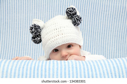 Baby with a knitted white hat