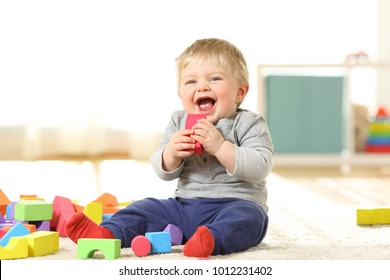 Baby laughing and playing with colorful toys sitting on a carpet at home