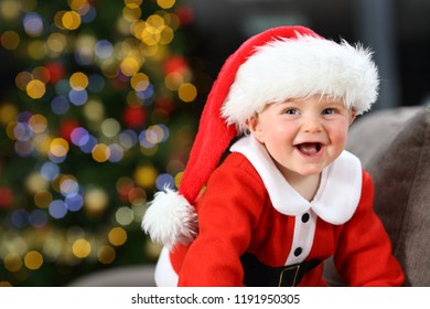Baby laughing wearing santa claus disguise on a couch at home in christmas with a tree in the background