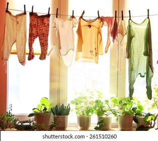 Baby laundry hanging on a clothesline with sun rising on a background