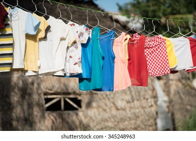 Baby laundry hanging on a clothesline with sun rising on a country background