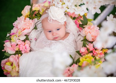 baby laying in basket covered with flowers
