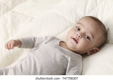 baby  laying on the bed
