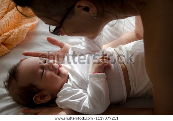 Baby laying on the bed smiling at his mom who is leaning over him.