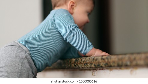 Baby learning to climb doorstep stair. Infant toddler development and effort.