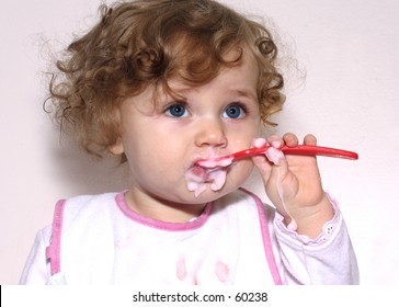 baby learning to feed herself with a spoon on white background