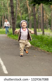 Baby Learning to Walk in Park. Cute Baby Boy learning to walk