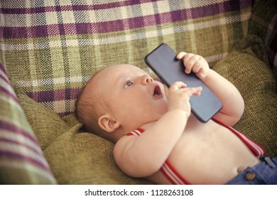 baby learns technology. New technology, modern life. Infant use mobile phone or smartphone. Baby boy with suspenders lie in armchair. Child development concept. Childhood, infancy, innocence.