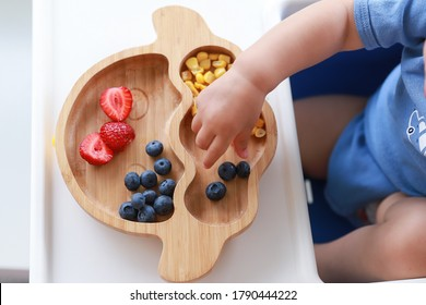 Baby led weaning (blw) top view little kid eating mix fruit strawberry,blueberry and corn on high chair. Baby eating finger food self-feeding. Fine motor development.