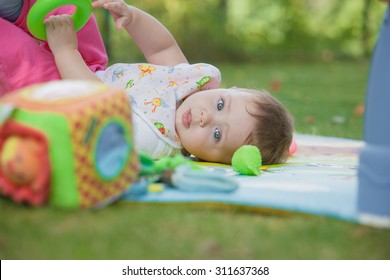Baby, less than a year old   playing with a toy on a background of green grass