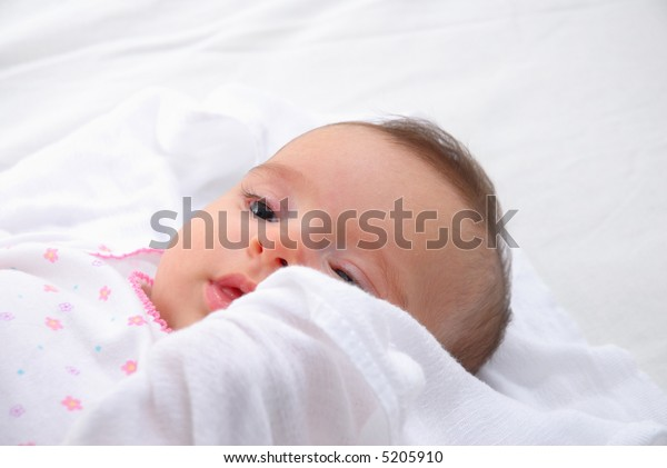 Baby lied down in the white bed .