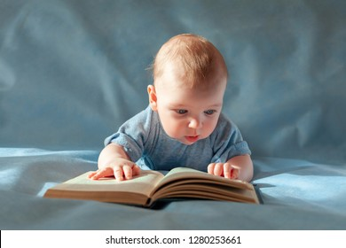 The baby lies on his stomach and reads an old book on a blue background.