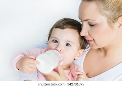 Baby little girl drinking a milk from bottle in the mom's arms.Shallow doff