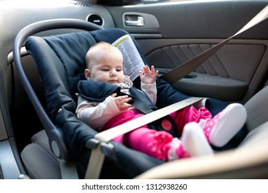 Baby little girl going for a safe drive in her nicely cushioned baby car seat