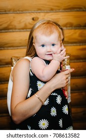 Baby little girl holds a finger in the mouth, on her hand mother sitting on the background of a wooden wall. Happy family. upper half. Looking the camera. Close up. emotions are amazed, surprise.