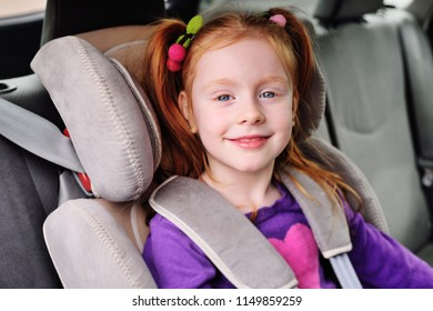 baby little red-haired girl smiling while sitting in a child car seat. Safe transportation of children in the car.