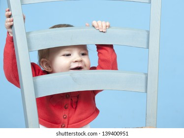 baby looking from behind a chair, isolated on blue