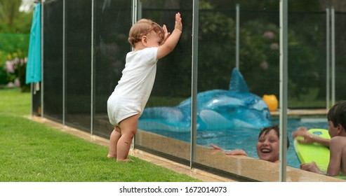 Baby looking at kids play inside swimming pool water during sumemr day. infant leaning on pool fence