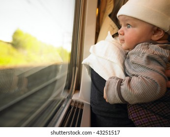 Baby looking out train window while being held by adult. Horizontally framed shot.