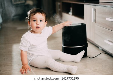 The baby looks at the humidifier. The concept of humidity in the home and health