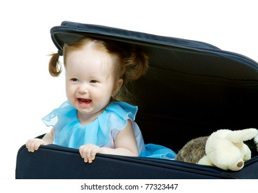Baby looks from a travel bag suitcase with toys