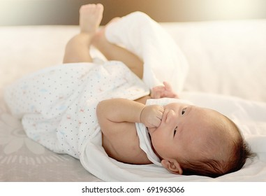 The baby is lying in bed. Product ideas about children, baby feeding, baby toys, family,Growth.
